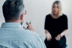 举行笔和谈判的治疗师的特写镜头 免版税库存图片