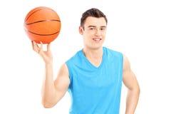 举行篮球和摆在的蓝球运动员 免版税库存照片