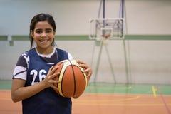 举行篮球的混合的族种女孩 免版税库存照片