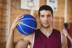 举行篮球的确信的蓝球运动员 库存图片