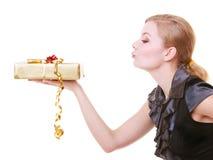 举行红色圣诞节礼物盒吹的亲吻的黑礼服的白肤金发的女孩 免版税库存照片