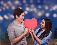 举行红色心脏形状的亚洲夫妇 库存照片