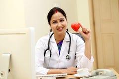 举行红色心脏形状的年轻印地安女性医生 图库摄影