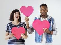 举行红色心脏爱和关系概念的愉快的人种间夫妇 免版税库存照片