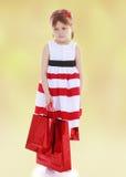 举行红色纸购物的一件镶边礼服的女孩 免版税库存图片