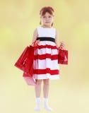 举行红色纸购物的一件镶边礼服的女孩 库存照片