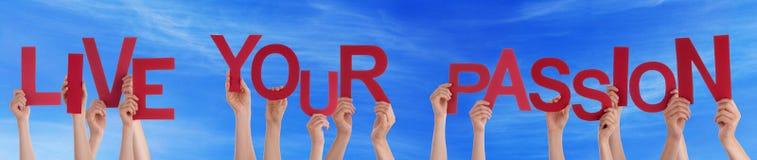 举行红色词的手居住您的激情蓝天 免版税库存图片