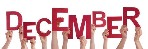 举行红色词12月的许多人手 免版税图库摄影