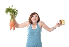 举行红萝卜和蛋糕健康营养的妇女 免版税库存照片