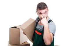 举行纸板做箱子神色的搬家工人人在我姿态 免版税图库摄影