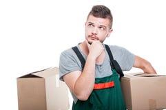 举行纸板箱和认为的搬家工人人 免版税库存图片