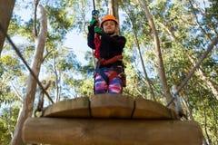 举行绳索和身分在木平台的小女孩佩带的盔甲 图库摄影