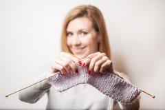 举行编织在手上的美丽的微笑的妇女 被弄脏的背景 图库摄影