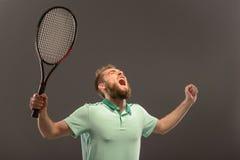 举行网球的球衣的英俊的年轻人 库存照片