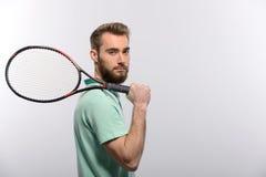 举行网球的球衣的英俊的年轻人 图库摄影