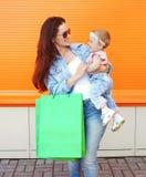 举行美丽的微笑的母亲递有购物袋的婴孩 库存照片