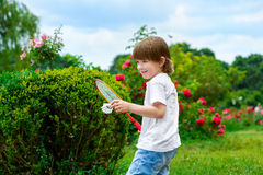 举行羽毛球的愉快的小男孩画象  库存照片