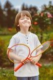 举行羽毛球的愉快的小男孩画象  免版税库存图片