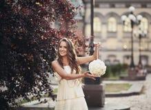 举行花束和微笑的一件白色礼服的年轻美丽的女孩 免版税库存照片