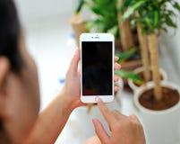 举行苹果计算机iPhone 6S加上的妇女 免版税库存照片