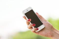 举行苹果计算机iPhone 5S的妇女手 图库摄影