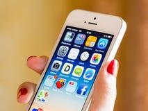 举行苹果计算机iPhone 5S的妇女手 免版税库存照片