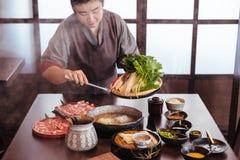 举行菜入火锅由钳子用Wagyu A5牛肉和在沙埠明白汤的妇女被切的Kurobuta与小河 库存图片