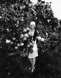 举行葡萄柚和身分的一个少妇的画象在果树园(所有人被描述不是更长生存和没有estat 免版税图库摄影
