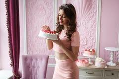 举行蛋糕和微笑的一件桃红色礼服的美丽的年轻高女孩 桃红色内部样式 免版税库存图片
