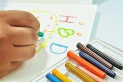 拿着蜡笔的手 免版税库存图片