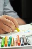 拿着蜡笔的手 免版税库存照片