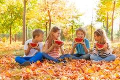 举行西瓜和吃的坐的孩子 免版税库存图片