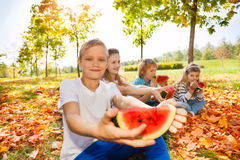 举行西瓜和吃的愉快的孩子 库存图片