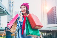 举行许多购物袋和微笑的一个激动的美丽的女孩穿戴衬衣和羊毛帽子的画象 复制空间 免版税图库摄影