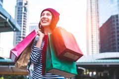 举行许多购物袋和微笑的一个激动的美丽的女孩穿戴衬衣和羊毛帽子的画象 复制空间 库存图片