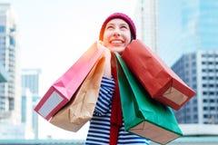 举行许多购物袋和微笑的一个激动的美丽的女孩穿戴衬衣和羊毛帽子的画象 复制空间 图库摄影