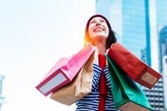 举行许多购物袋和微笑的一个激动的美丽的女孩穿戴衬衣和羊毛帽子的画象 复制空间 库存照片