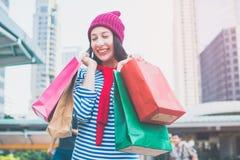 举行许多购物袋和微笑的一个激动的美丽的女孩穿戴衬衣和羊毛帽子的画象 复制空间 免版税库存图片