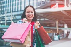 举行许多购物袋和微笑的一件激动的美丽的女孩穿戴衬衣的画象 复制空间 库存图片