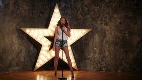 举行话筒和唱歌的性感的女孩 光亮的星形 股票录像