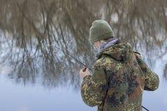 举行诱剂在他的手上的渔夫他在钓鱼前检查诱饵 免版税库存图片