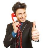 举行赞许的商人在电话期间 库存照片