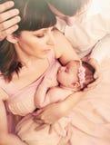 举行逗人喜爱睡觉一点女婴机智的有同情心的慈爱的父母 库存照片