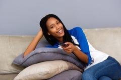 举行遥控放松在沙发和看电视的美丽的年轻非洲妇女 库存图片