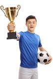 举行金战利品和橄榄球的少年足球运动员 库存照片