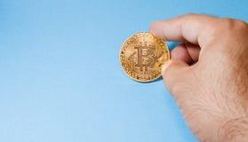 举行金黄Bitcoin的手 库存照片