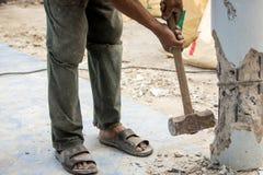 举行锤子和抽杀的工作者对具体堆 免版税图库摄影