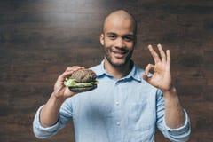 举行鲜美汉堡包和显示的微笑的年轻人好标志 免版税库存照片