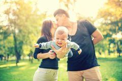 举行婴儿和亲吻的已婚夫妇 愉快的家庭、父母天概念 免版税图库摄影