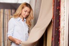 举行织品和微笑的白肤金发的女孩 免版税库存照片